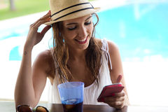 Beautiful girl taking a mobile phone at the swimming pool. Royalty Free Stock Photography