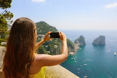 Beautiful girl taking picture in Capri Island with Faraglioni se royalty free stock image