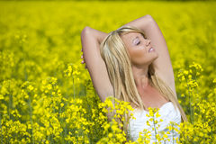 A beautiful girl taking in rays in a yellow field Stock Photo