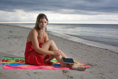 Beautiful girl taking a rest when reading. At the beach, on sunset Stock Photo