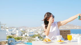 Beautiful girl taking selfie on breakfast with phone at outdoor cafe with amazing view on Mykonos town. Beautiful elegant lady on breakfast with phone at stock video