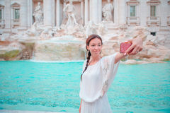 Beautiful girl taking selfie by the Fountain of Trevi in Rome. Happy woman enjoy her european vacation in Italy Royalty Free Stock Photos