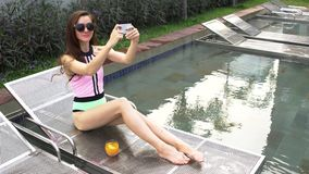 Beautiful girl taking selfie and laughing at the swimming pool in luxury villa. Woman with coctail orange juice in tropical resort royalty free stock photo
