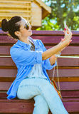 Beautiful girl taking a selfie. In park stock images