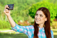 Beautiful girl taking selfie in the park Stock Image