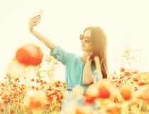 Beautiful girl taking selfie in poppies meadow. stock photos