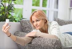 Beautiful girl taking selfie on sofa Royalty Free Stock Photos