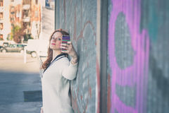 Beautiful girl taking a selfie in an urban context Royalty Free Stock Image