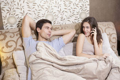 Beautiful girl talking on the cell phone while laying in the bed with her boyfriend Royalty Free Stock Photos