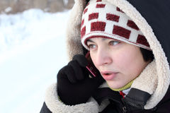 Beautiful girl talking by mobile phone. In winter royalty free stock photos