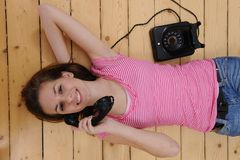 Beautiful girl talking on phone. Beautiful girl lying on the floor and talking on phone at home stock photo