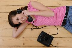 Beautiful girl talking on phone. Beautiful girl lying on the floor and talking on phone at home royalty free stock images