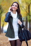 Beautiful girl talking on phone in autumn. Royalty Free Stock Photos