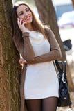 Beautiful girl talking on phone in autumn. Royalty Free Stock Image
