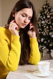 Beautiful girl talking on phone in cafe, background of Christmas tree Stock Photos