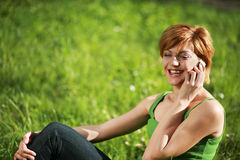 Beautiful girl talking on the phone in the grass. Smiling beautiful girl talking on the phone lying on the grass stock images
