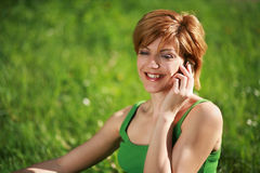 Beautiful girl talking on the phone in the grass. Smiling beautiful girl talking on the phone sitting on the grass royalty free stock photo