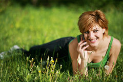 Beautiful girl talking on the phone on the grass. Smiling beautiful girl talking on the phone lying on the grass royalty free stock images