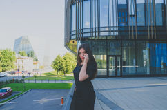 Beautiful girl talking on the phone near business center Royalty Free Stock Photos