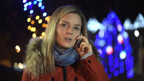 Beautiful girl talking phone in the night city stock video