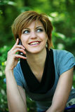 Beautiful girl talking on the phone in the park. Smiling beautiful girl talking on the phone in the park stock image