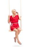 Beautiful girl talking on phone seated on a swing Stock Image