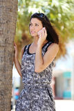 Beautiful girl talking on the phone in the street. Young girl smiling while talking on the phone Royalty Free Stock Image
