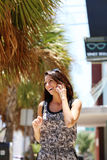 Beautiful girl talking on the phone in the street. Young girl smiling while talking on the phone Royalty Free Stock Photos