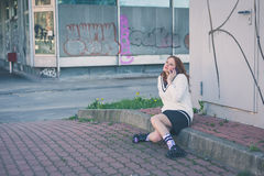 Beautiful girl talking on phone in an urban context Stock Photography