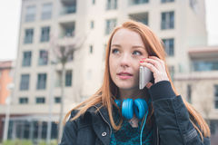 Beautiful girl talking on phone in an urban context Royalty Free Stock Image