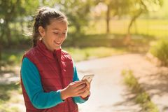Beautiful girl talking on a smartphone in a red vest stock image