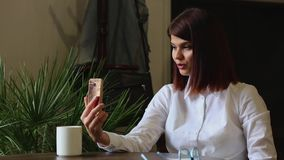 Beautiful girl talking to business partners using a mobile phone camera. Beautiful girl talking to business partners using a mobile phone camera stock video