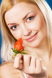 Beautiful girl tasting a strawberry Stock Photography