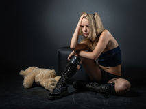 Beautiful girl - teen anime style. Beautiful teenager with blond hair in the style of anime in black army boots sitting on the dirty floor royalty free stock photo
