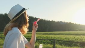 Beautiful girl teenager in a hat blowing soap bubbles stock video footage