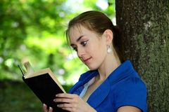 Beautiful girl  teenager reads the book in park Stock Photos