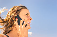 Beautiful girl telephoning on the beach Stock Photos