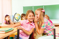 Beautiful girl tells secret to other in school Stock Image