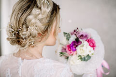 Beautiful girl in tender lacy dress with bouquet flowers peonies in hands standing against floral background in flower shop. Joyfu Stock Photos