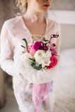 Beautiful girl in tender lacy dress with bouquet flowers peonies in hands standing against floral background in flower shop. Joyfu Royalty Free Stock Image