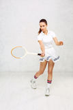 Beautiful girl in tennis clothes, brandishing a tennis racket on Royalty Free Stock Image
