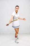 Beautiful girl in tennis clothes, brandishing a tennis racket on Royalty Free Stock Photo