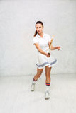 Beautiful girl in tennis clothes, brandishing a tennis racket on Royalty Free Stock Photos