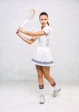 Beautiful girl in tennis clothes, brandishing a tennis racket on Stock Image