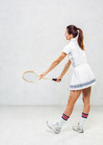 Beautiful girl in tennis clothes, brandishing a tennis racket on Stock Photo