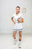 Beautiful girl in tennis dress, standing with a tennis racket in Royalty Free Stock Image