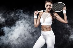 Beautiful sport woman tennis player with racket in white sportswear costume. Beautiful girl tennis player with a racket on dark background wiht lights Stock Photos