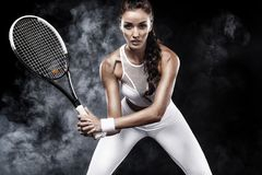 Beautiful sport woman tennis player with racket in white sportswear costume. Beautiful girl tennis player with a racket on dark background wiht lights Stock Images