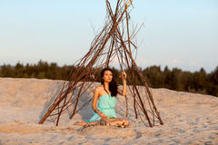 Beautiful girl in a tent shaman. royalty free stock images