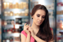 Beautiful Girl Testing Perfume in a Cosmetics Shop. Shopping woman looking for the best scent in a perfumery Stock Photo